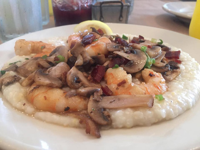 Sautéed shrimp with mushrooms, scallions & bacon served over cheese grits from Hominy Grill