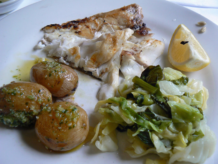Branzino served with potatoes and greens