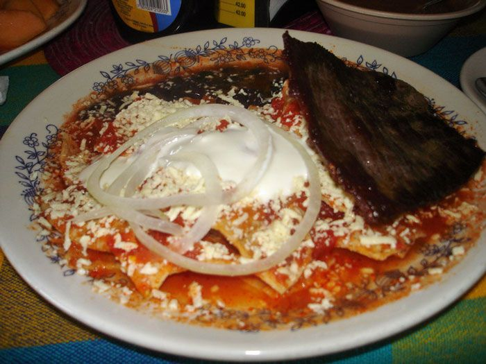 Red chilaquiles served with scrambled eggs, beans and tasajo.