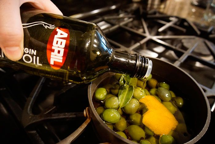Pour the Aceites Abril Extra Virgin Olive Oil to cover the olives in a pot.