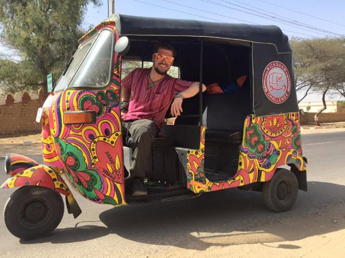 Will Hatton driving a multi-colored tuk tuk across India