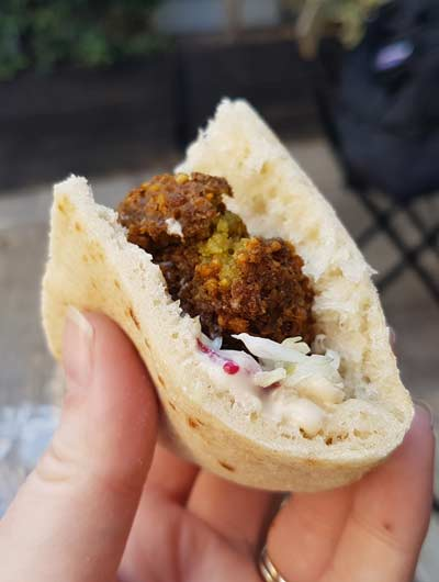A pita stuffed with crispy delicious green falafel